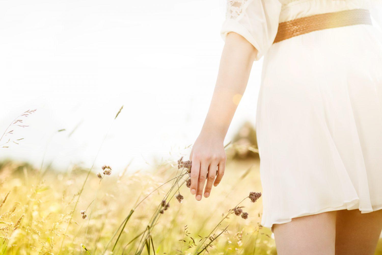 Die querformatige Detailfotografie zeigt im goldenen Schnitt ein Model in kurzem, weißen Kleid, das mit der Hand durch die Gräser streicht und wurde von dem Fotograf Fritz Phillipp aus Frankfurt im Rhein-Main-Gebiet bei Bad Vilbel aufgenommen