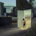 """Das surrealistische Foto aus der Serie """"Triologie der Türen"""" für die Darmstädter Tage der Fotografie zeigt einen kleinen Jungen mit Wasserpistole, der durch eine auf einer dunklen Straße stehende Zimmertür auf den sonnigen Sandstrand blickt, von dem Fotografen Fritz Phillipp aus Frankfurt im Rhein-Main-Gebiet"""