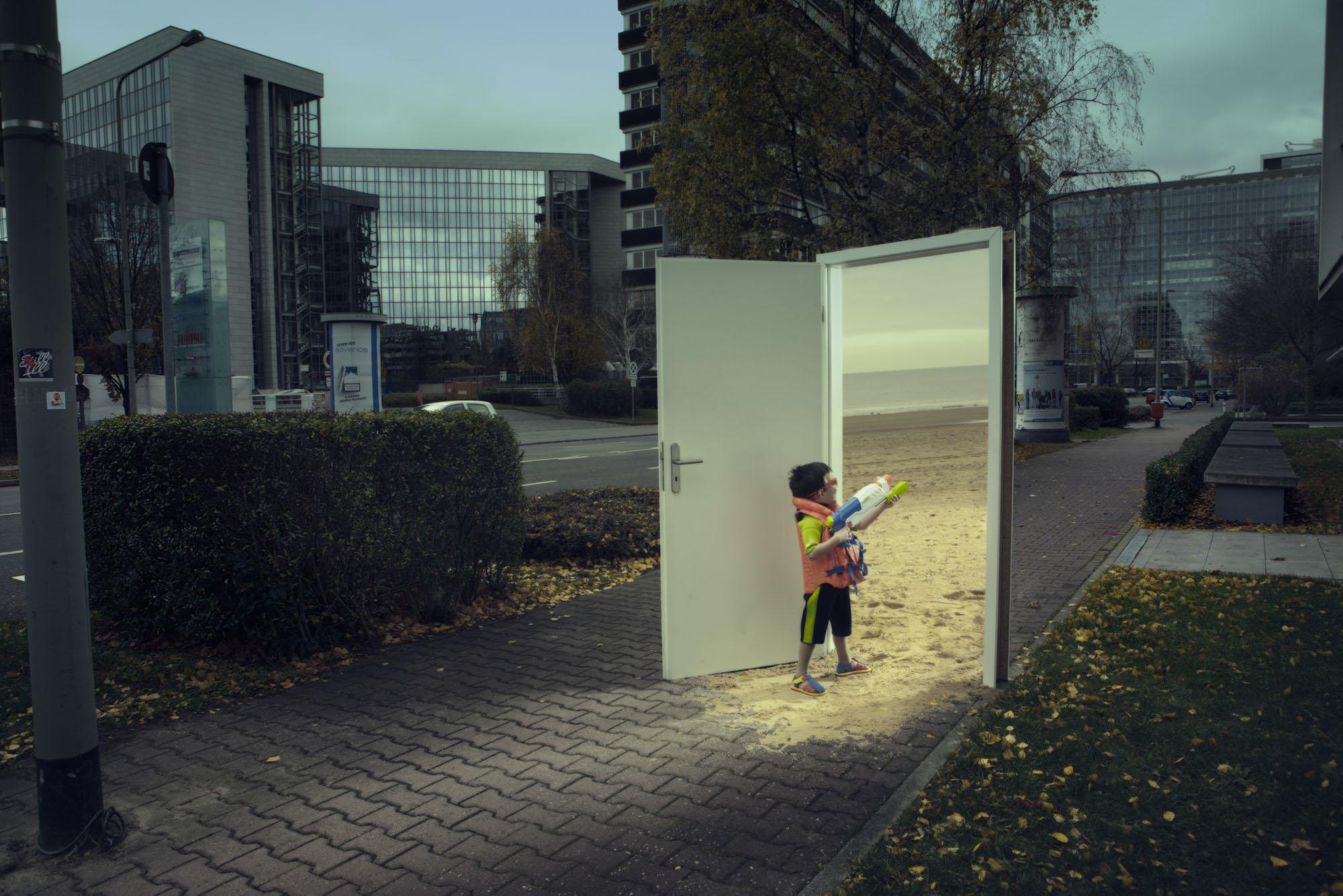 """Das surrealistische Foto aus der Serie """"Triologie der Türen"""", zeigt einen kleinen Jungen mit Wasserpistole, der durch eine auf einer dunklen Straße stehende Zimmertür auf den sonnigen Sandstrand blickt, von dem Fotografen Fritz Phillipp aus Frankfurt im Rhein-Main-Gebiet"""