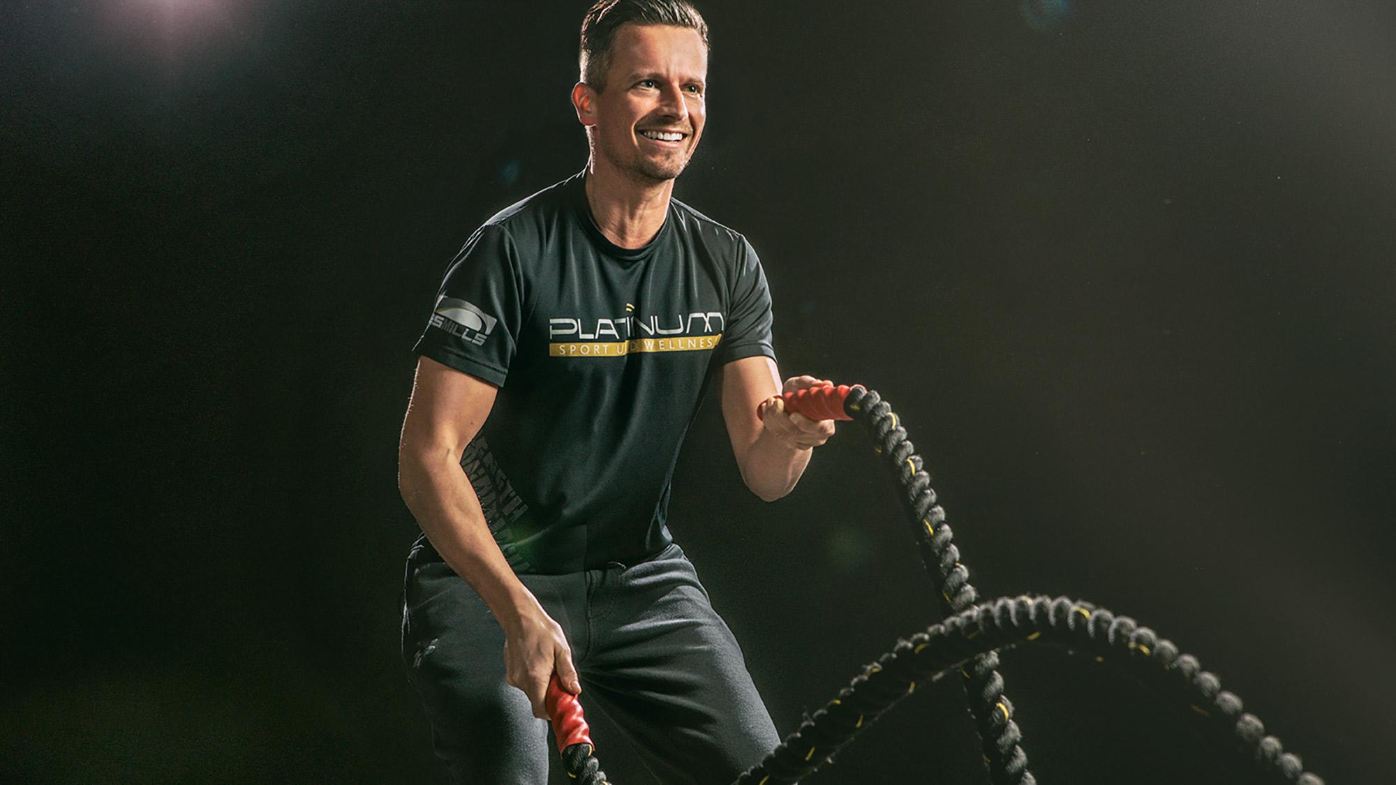 Dieses dynamische Fitnessfoto aufgenommen von dem Frankfurter Fotografen Fritz Philipp zeigt einen Sportler vor schwarzem Hintergrund der mit viel Spaß Seile schwingt