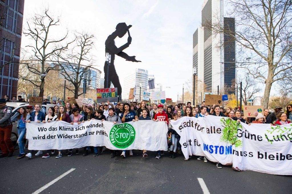 """Das Foto von fritzphilipp photography zeigt im Hintergrund den """"Hammering Man"""" in Frankfurt während die Schüler mit Plakaten durch die Straße laufen"""