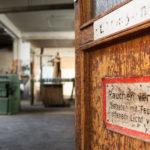Die Aufnahme des Frankfurter Fotografen Fritz Philipp zeigt den Eingangsbereich einer alten Schreinerei, im Vordergrund ist die Holztür mit alten Schildern zu sehen, im Hintergrund die weitläufige Industriehalle, die zu einem Mietstudio wird, 2020: Great things to come